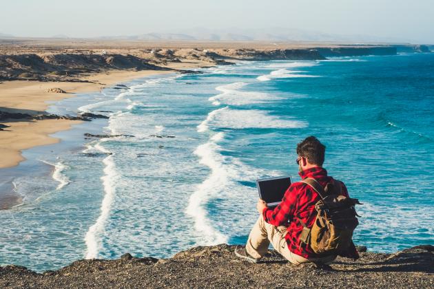homem com computador e vista para a praia